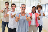 Business people giving thumbs up to camera and smiling