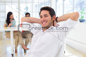 Businessman relaxing with coworkers in background