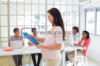 Pregnant casual businesswoman carrying folder