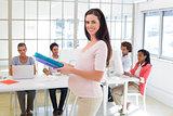 Pregnant office worker walking with folders