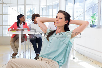 Attractive office worker relaxing with colleagues working behind