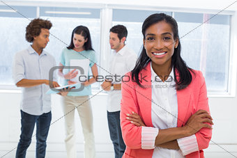 Businesswoman smiling to camera with colleagues in background