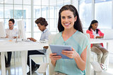 Businesswoman on tablet pc smiling at camera
