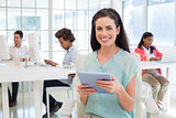 Businesswoman on tablet pc smiling at camera with colleagues behind