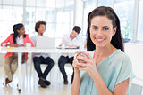 Attractive businesswoman drinking hot beverage with colleagues in background