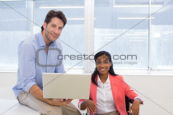 Office Workers with laptop smiling to camera