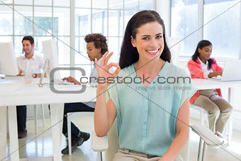 Attractive businesswoman giving OK sign to camera