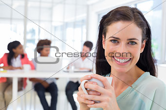 Attractive businesswoman drinking coffee with coworkers in background