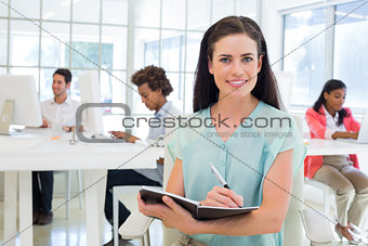 Attractive businesswoman writing in notebook and smiling to camera