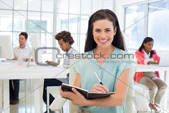 Attractive businesswomen writing in notebook with colleagues behind her