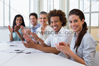 Business people clapping and smiling at camera