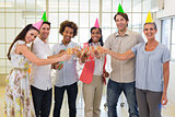 Colleagues celebrate success by having a party and smile at camera