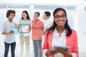 Attractive businesswoman smiling at camera while colleagues are standing behind