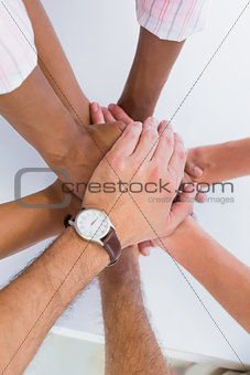 Team members putting hands together