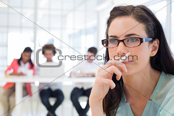 Attractive casual businesswoman holding pencil focusing