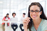 Attractive businesswoman smiling at camera with coworkers in background