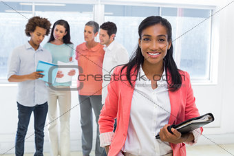 Attractive worker with planner smiles at camera with colleagues in background