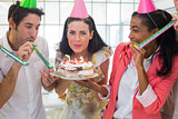 Businesswoman blowing out candles on cake