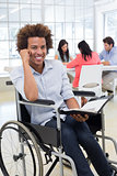 Businessman in wheelchair holding planner and smiling at camera