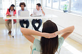 Businesswoman relaxes with hands behind her head