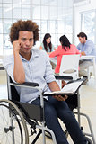 Stern businessman in wheelchair holds planner and frowns at camera