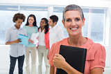 Businesswoman holds planner and smiles at camera while colleagues stand behind