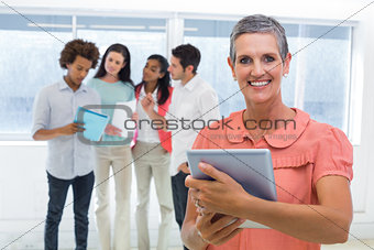 Businesswoman smiles at camera while looking at tablet pc with coworkers behind her