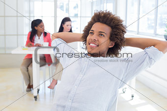 Businessman relaxing with coworkers behind him