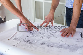 Architects working on blueprints together