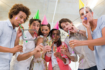 Business people celebrating at the workplace with glasses of champagne
