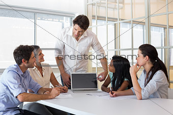 Attractive businessman speaking to coworkers