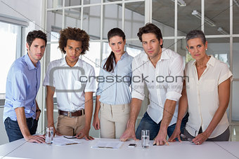 Casual business team having a meeting looking at camera