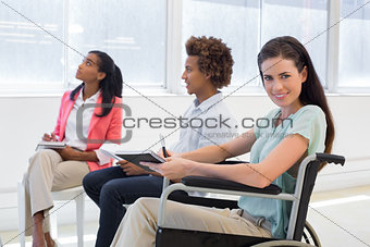 Attractive businesswoman in wheelchair smiling in the workplace