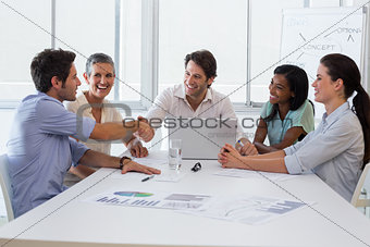 Handsome coworkers shaking hands in approval
