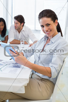 Pretty businesswoman using tablet device in business meeting