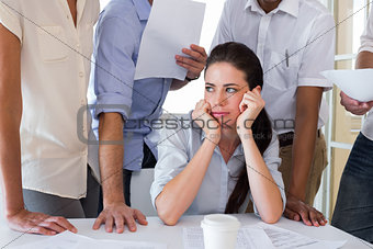 Worried businesswoman surrounded by colleagues