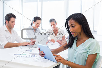 Attractive businesswoman using tablet with coworkers behind