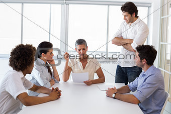 Serious businesswoman speaking to her coworkers