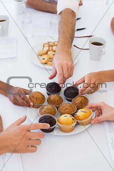 Business people taking muffins from plate