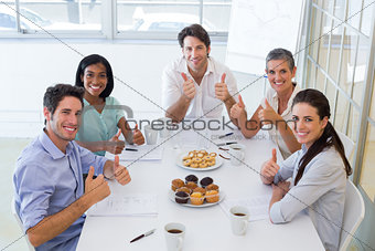 Business people eating muffins give thumbs up to camera