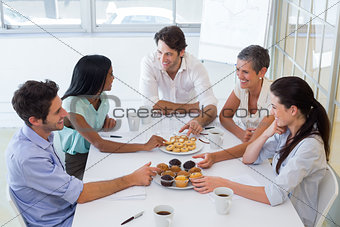 Business people chat while eating muffins and drinking coffee