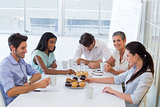 Work colleagues having hot beverages and muffins