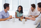 Work colleagues chatting in board room while enjoying coffee and muffins