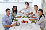 Workers smile at camera while eating healthy lunch