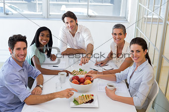 Business people smiling at camera eating sandwiches and fruit for lunch