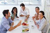 Workers laugh while eating sandwiches for lunch