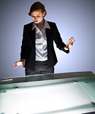 Redhead businesswoman standing and gesturing by a desk