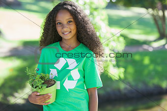 Young environmental activist smiling at the camera holding a potted plant
