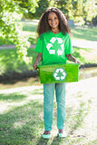 Young environmental activist smiling at the camera holding box