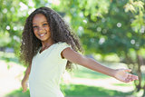 Young girl smiling at the camera with arms outstretched